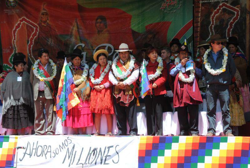 """In der Mitte der Tribüne: der Gouverneur von La Paz, Cesar Cocarico, links von ihm Nilda Copa, rechts Nardi Suxo - und Transparent: """"Jetzt sind wir Millionen"""""""