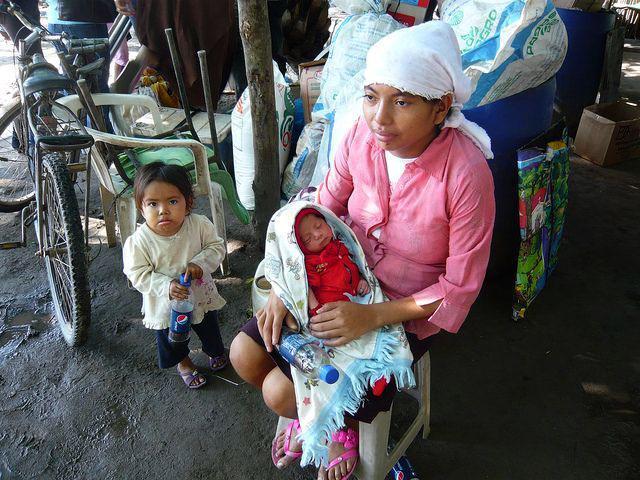 Mutter mit ihrem neugeborenen Kind vor ihrem Hab und Gut.