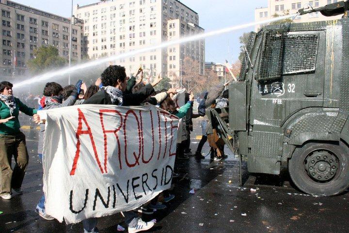 Studierende der Architekturfakultät blockieren einen Wasserwerfer