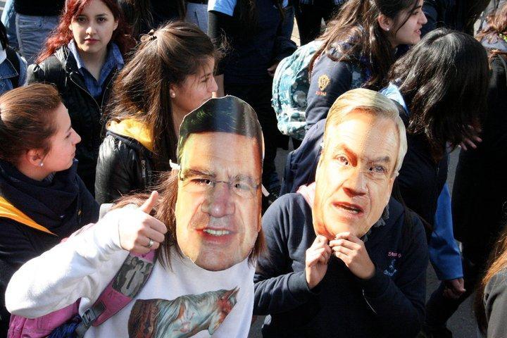 Demonstranten mit Masken: links  Bildungsminister Lavin, rechts Präsident Piñera