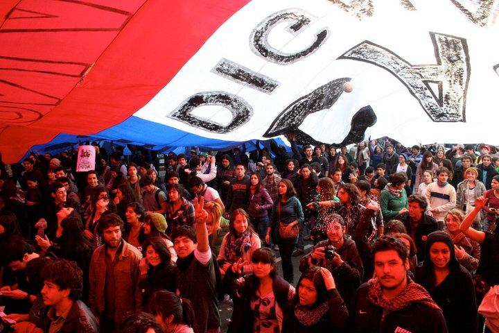 Demonstranten unter einer riesigen chilenischen Flagge