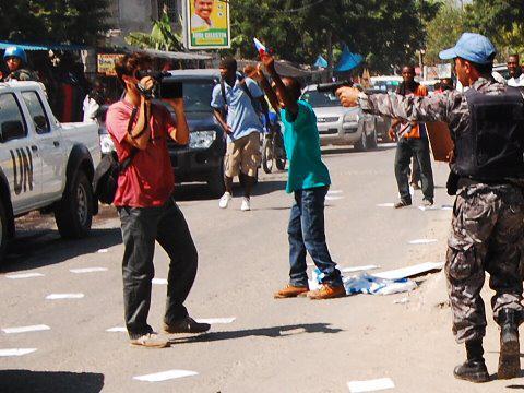 Repression der Minustah: Ein UNO-Soldat droht einem Journalisten ihn zu erschießen, wenn er nicht aufhört zu filmen.  Oktober 2010, Port-au-Prince, Haiti