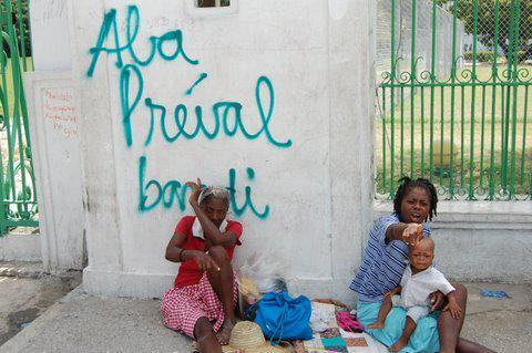 """Vor dem Nationalpalast warten ganze Familien auf Touristen, die die Ruinen sehen möchten. Hinter ihnen steht an """"Nieder mit Préval"""". Gemeint ist der Präsident René Preval.  Juni 2010, Port-au-Prince, Haiti"""