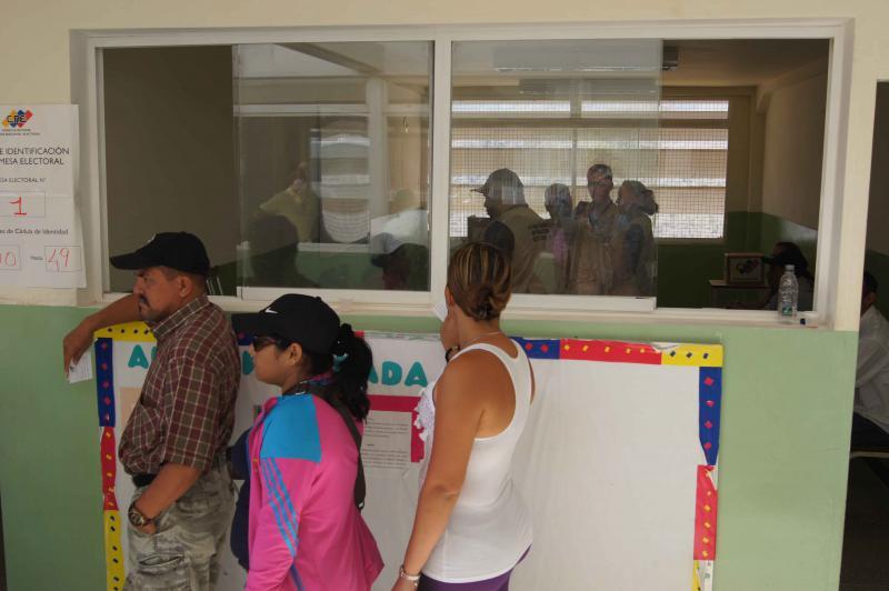 Wählerinnen und Wähler warten vor dem Wahlbüro in einer Schule in Ciudad Caribia