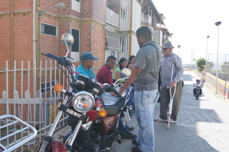 Wählerinnen und Wähler warten nach der Stimmabgabe in Ciudad Caribia mit ihren Nachbarn auf der Straße