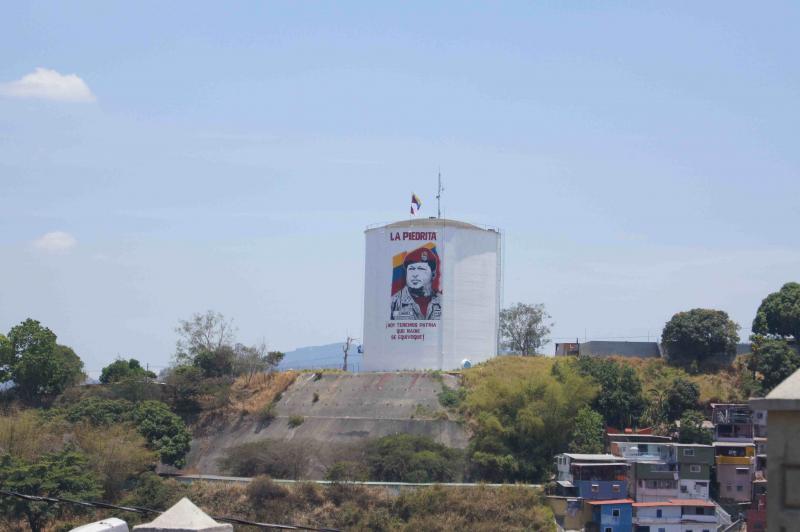 Mitglieder des Kollektivs La Piedrita haben an einem Wasserspeicher über dem Stadtteil 23 de Enero ein Bild von Hugo Chávez angebracht.
