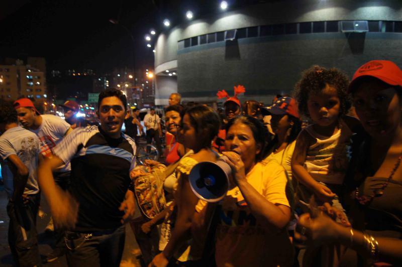 """Die Menschen skandieren Parolen gegen die Opposition: """"Majunche, de pana, te queda una semana!"""" (Schönling, wirklich, dir bleibt eine Woche!)"""