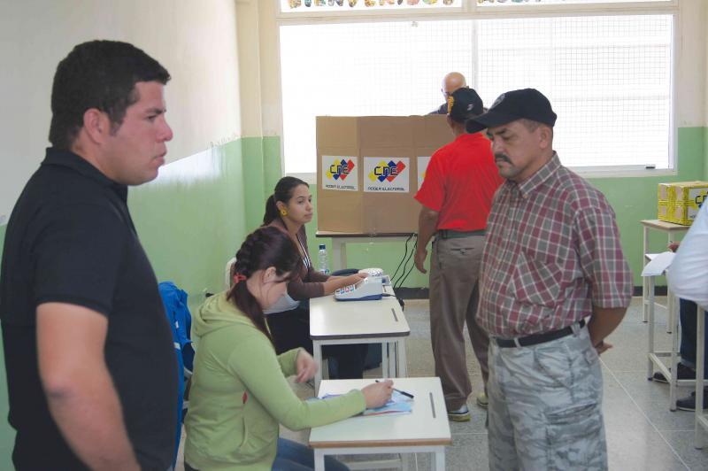 Am Wahltisch prüft eine Mitarbeiterin die Personaldokumente des Wählers. Am zweiten Tisch wird das Gerät durch die biometrischen Informationen des Wähler freigeschaltet. Hinter der Sichtwand (hinten Mitte) steht der Wahlcomputer und das Tablett. Nach der Abgabe der Stimme wirft der Wähler den Papierbeleg in die Urne (hinten rechts).