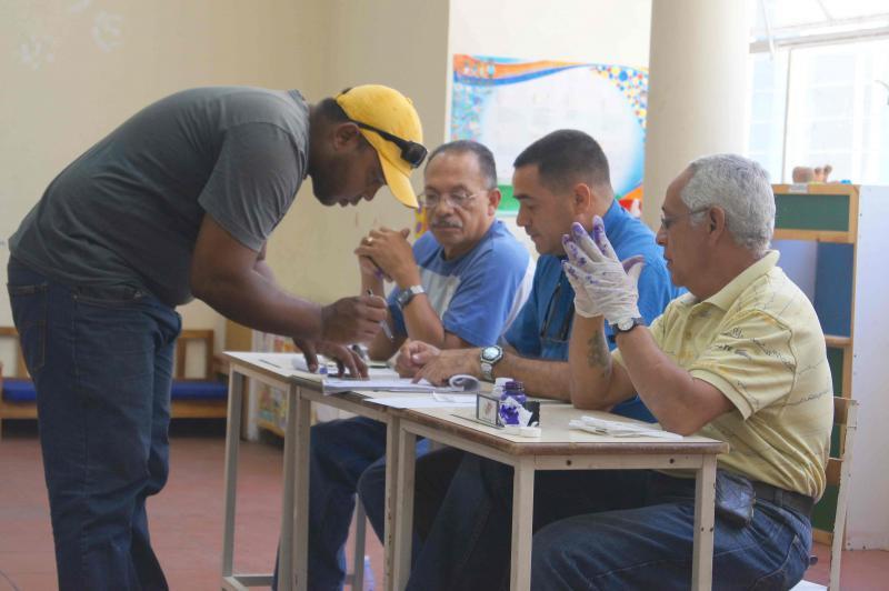 Danach zeichnet er in der Wahlliste seine Anwesenheit und den korrekten Ablauf des Wahlgangs ab und wird mithilfe blauer Farbe markiert, damit er an diesem Tag nicht noch einmal wählen gehen kann.