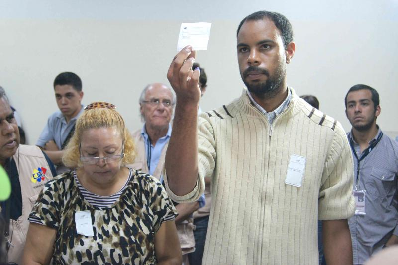 Jeder einzelne Beleg wird hochgehoben und laut vorgelesen. Der Wahltischmitarbeiter nennt jeweils die Partei und den Kandidaten.