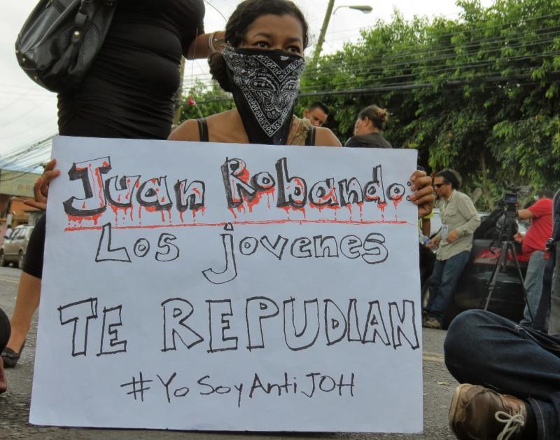 """Studentin mit Plakat """"Juan du stiehlst - die Jugend lehnt dich ab"""""""