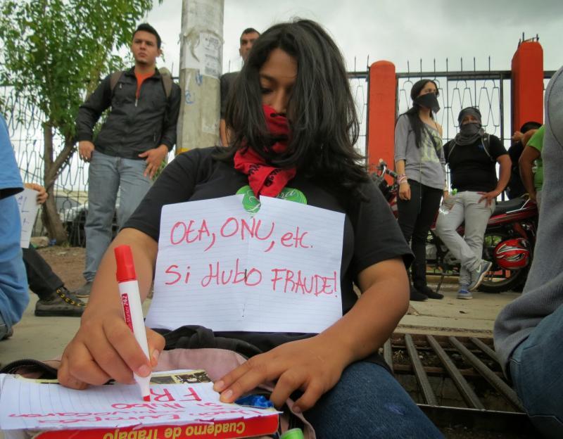 """Demonstrantin mit Schild """"OAS, UNO - es gab Wahlbetrug"""""""