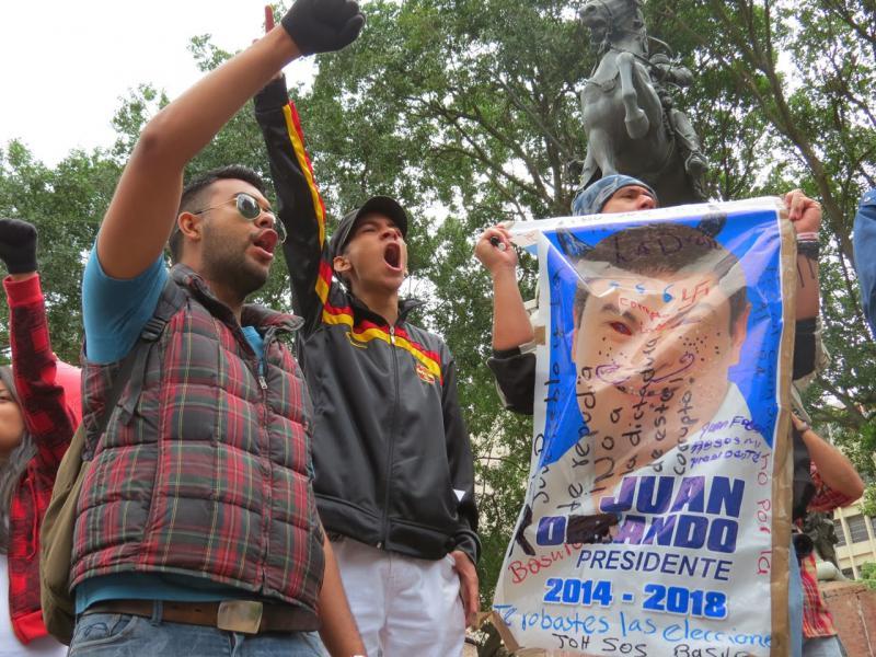 Demonstranten mit Wahlplakat von Juan Orlando Hernández, auf dem er als Dieb und Korrupter bezeichnet wird