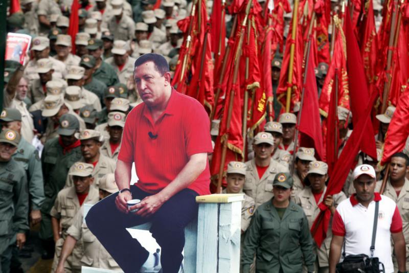Ein Demonstrationsteilnehmer trägt eine Installation mit dem Bild des verstorbenen Präsidenten Hugo Chávez