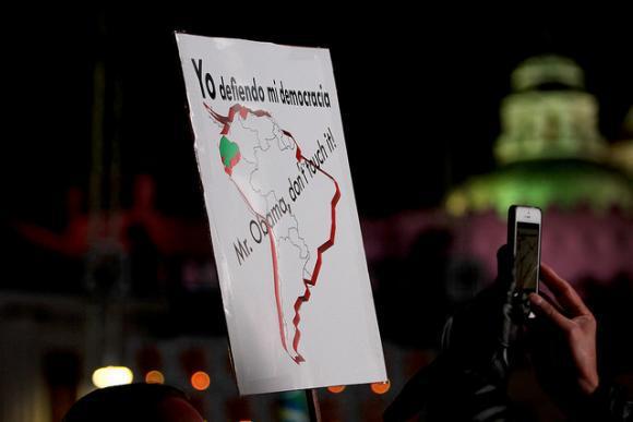 """Plakat: """"Ich verteidige meine Demokratie – Fassen Sie sie nicht an, Herr Obama"""". Eine Anspielung auf politische Spannungen zwischen der linksgerichteten Regierung Ecuadors und den USA"""