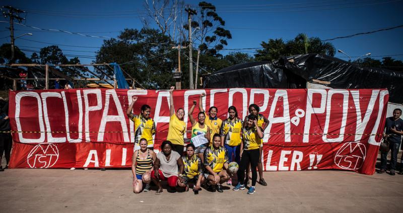 Frauenmannschaft vor dem Transparent der MTST zur Besetzung des Geländes