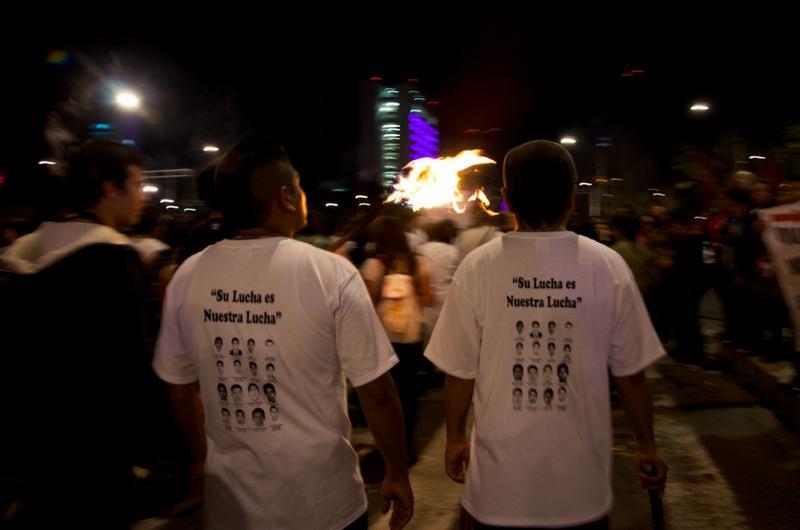 """Junge Männer tragen T-Shirts mit Fotos der verschwundenen Studenten. Schriftzug: """"Ihr Kampf ist unser Kampf"""""""