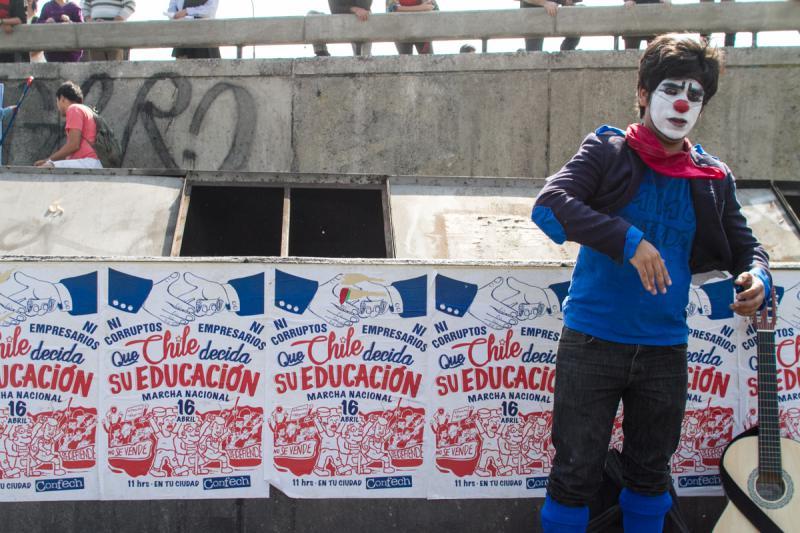 """Ein Clown posiert vor dem Plakat mit dem Aufruf zur Demonstration. Darauf steht: """"Weder Korrupte noch Unternehmer. Chile soll über seine Bildung entscheiden"""""""
