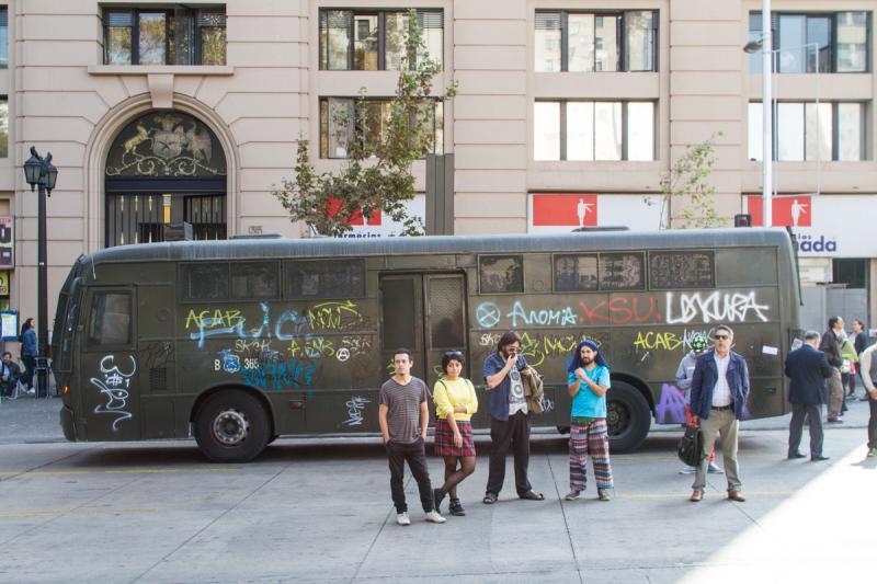 Demonstranten vor einem besprühten Bus der Polizei ...
