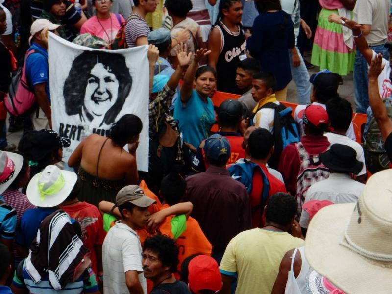 Demonstrierende versammeln sich mit dem Anlitz von Berta Cáceres. Als Studentin gründete sie den Rat der Indigenen und Volksorganisationen von Honduras (COPINH), der sich gegen Landraub, Abholzung, Bergbau und Geschlechtergewalt einsetzt
