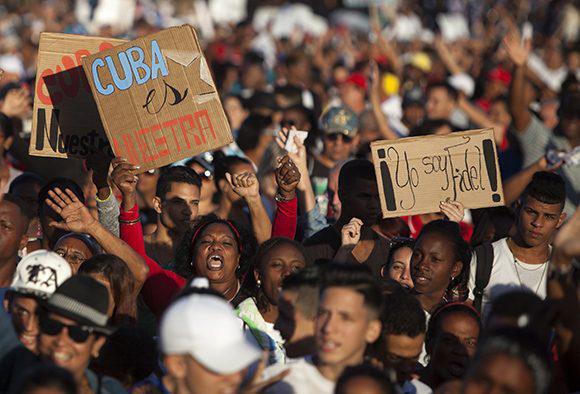 """Teilnehmerinnen der Demonstration halten Schilder hoch: """"Kuba gehört uns"""" und """"Ich bin Fidel""""."""