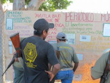 Aktivisten der CRAC vor einer Wandzeitung mit aktuellen Informationen