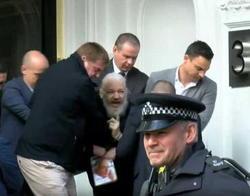 Julian Assange bei seiner Festnahme in der ecuadorianischen Botschaft in London durch britische Polizisten