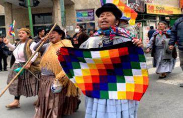 Frauen demonstrieren mit der indigenen Fahne gegen den Rassismus der Putsch-Regierung
