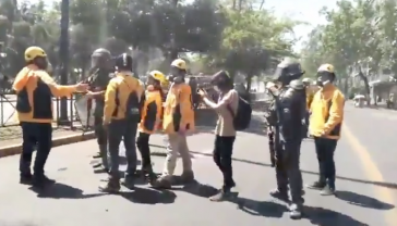 Mitarbeiter des Institutes für Menschenrechte – in gelben Jacken – vermitteln zwischen Polizei und Demonstranten