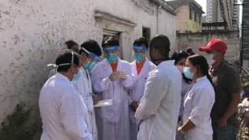 Ärzte aus China gehen mit Mitarbeitern eines Diagnosezentrums in Los Jardines de El Valle in Caracas von Haus zu Haus