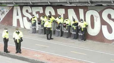 """Auf der Mauer hinter der Polizei steht das Wort """"Mörder"""""""