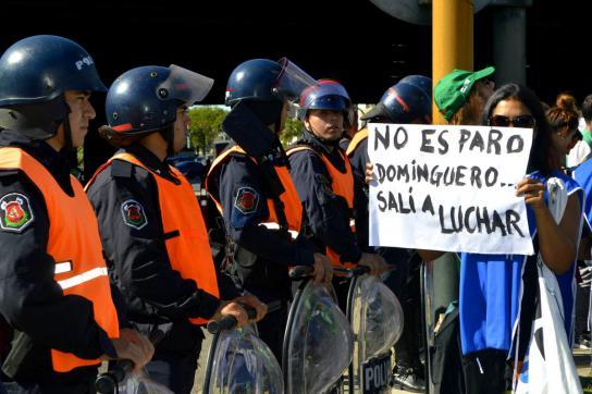 Streikteilnehmerin stellt sich Polizisten entgegen