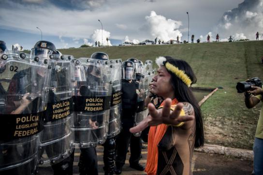 Indigene Frau vor Angehörigen der Militärpolizei