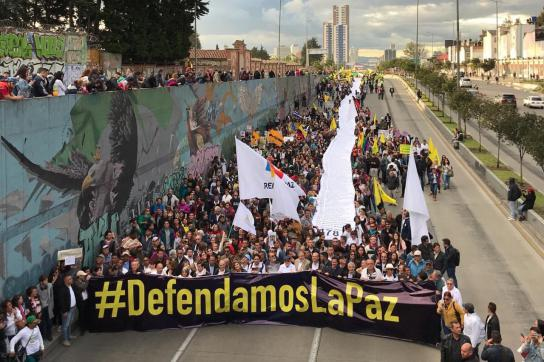 viele Menschen laufen protestierend auf der Straße in Kolumbien und halten ein Banner hoch mit dem Titel #Defendamoslapaz