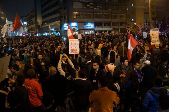 """Demonstrierende in Lima. Jemand hält ein Schild mit dem Spruch """"Que se vayan todos"""" hoch."""
